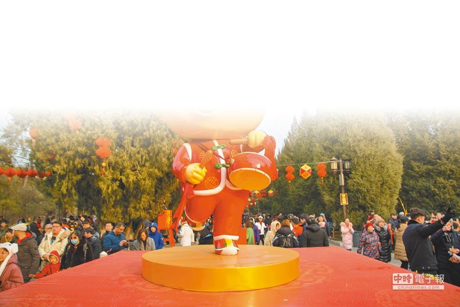 北京地壇春節廟會人山人海,遊客紛紛和「金豬歡歡」合影留念。(CFP)