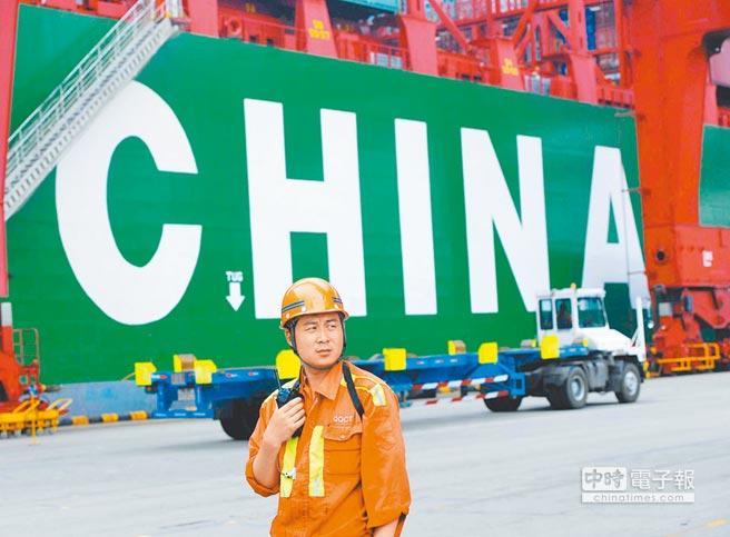 青島港外貿貨櫃碼頭,一名工人指揮貨櫃裝卸。(新華社資料照片)