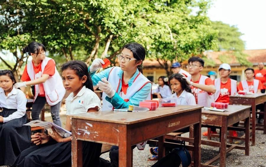 為了能夠評估寄生蟲防治計畫的成效,北醫大團隊到柬埔寨為學童進行頭蝨感染率的調查。(教育部提供)