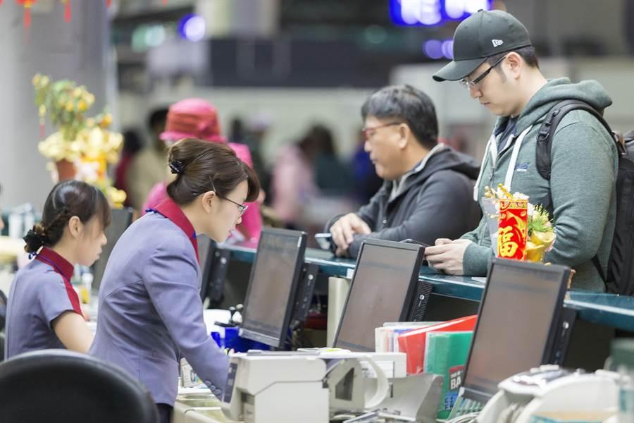 圖為華航地勤人員為旅客辦理登機手續情形。(資料照 陳麒全攝)
