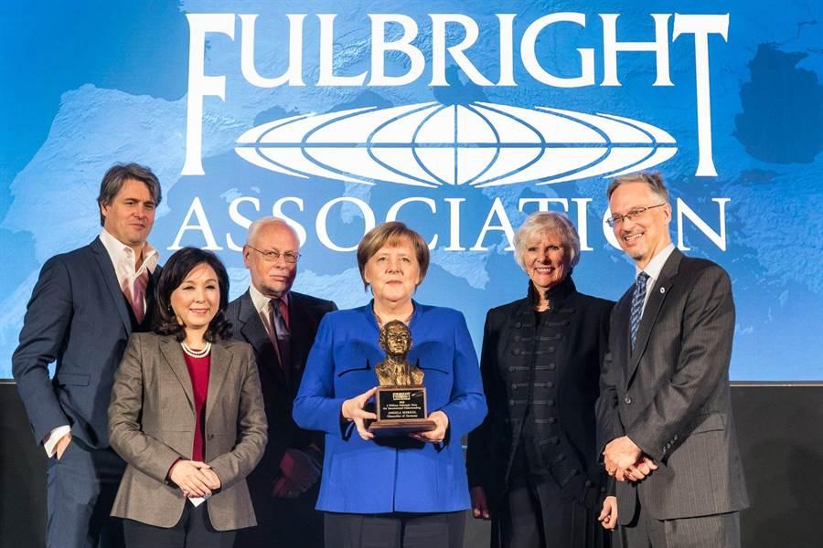 新光金控副董事長李紀珠(前左1)與傅爾布萊特獎2018年得獎者德國總理梅克爾(中藍衣者),在台上合影並短暫互動。(李紀珠臉書)