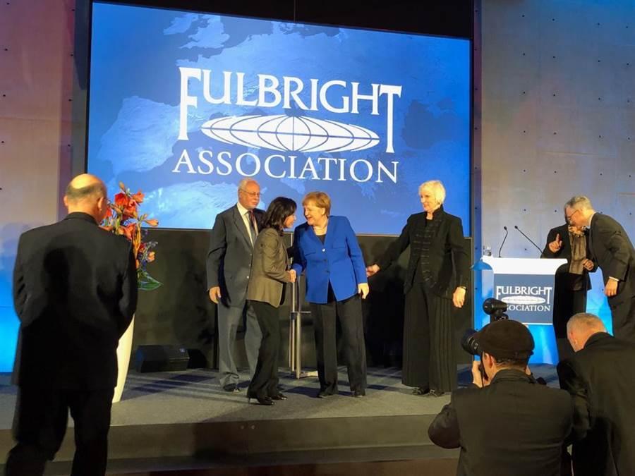 新光金控副董事長李紀珠與德國總理梅克爾,在傅爾布萊特頒獎台上短暫互動。(李紀珠臉書)