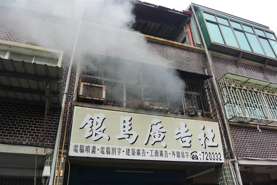 廣告社起火,濃煙竄出屋外。(巫靜婷攝)