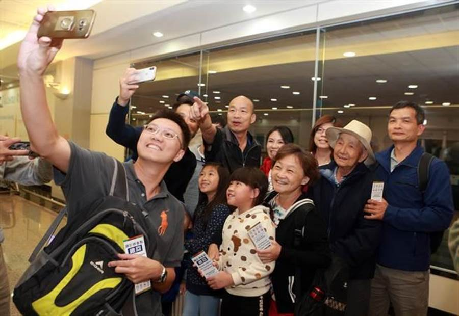 高雄市長韓國瑜在7日晚間返台,一下機就被熱情的民眾拉去合影。(陳麒全攝)