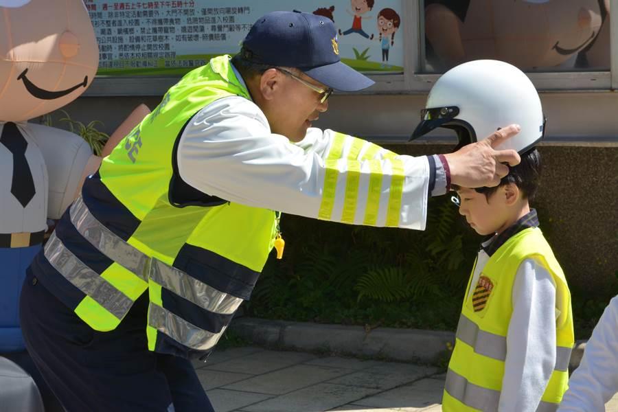 員警大哥哥細心為學童們換上警用背心與安全帽。(謝瓊雲攝)