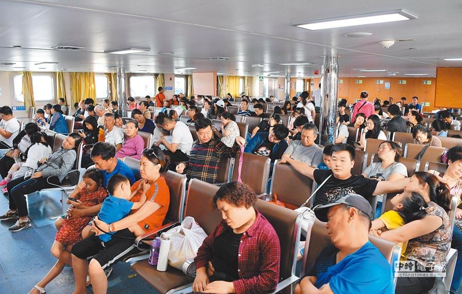 2月9日,眾多旅客在海口秀英港內的紫荊22號客滾船上的客艙內。(新華社)