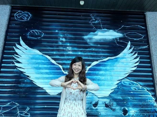 花蓮黎明教養院公關李庭慧充當天使,在「銀河之翼」傑作前合照留念。(范振和攝)