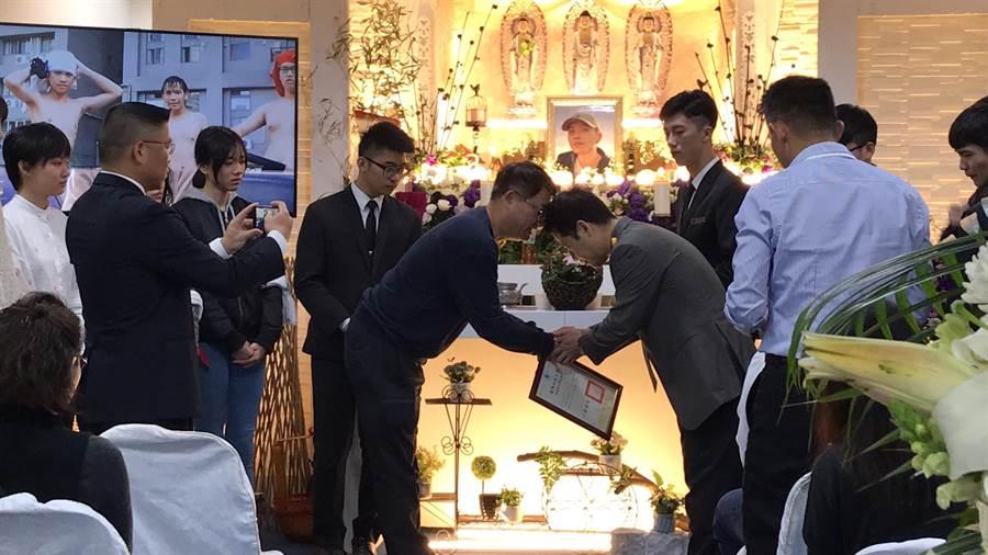 彭姓大學生14日舉辦告別式,其師長同窗好友都到場致意,班導師也特到場頒發畢業證書給彭父。(馮惠宜攝)