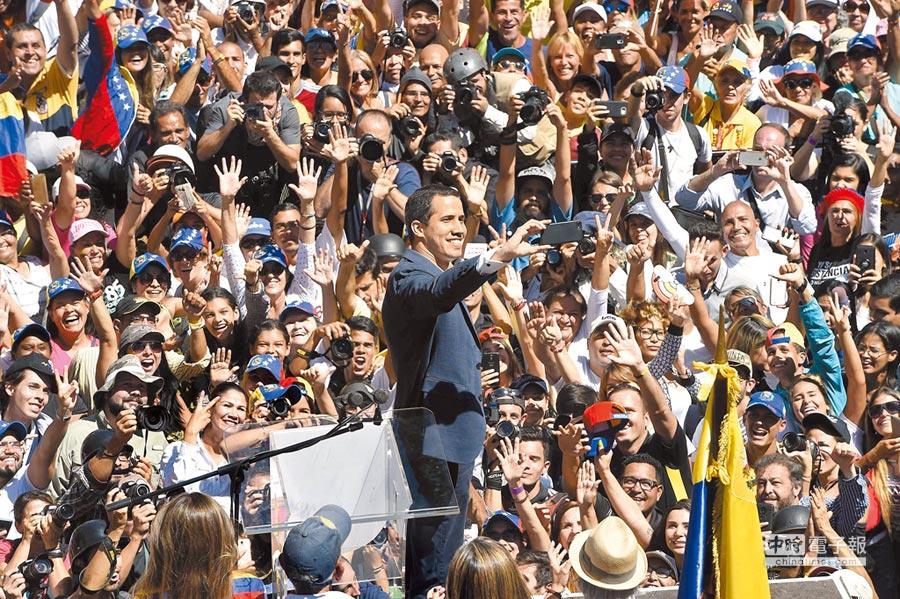 委內瑞拉反對派領袖、自任「臨時總統」的瓜伊多(中)12日在首都卡拉卡斯一場要求軍方放行美國援助的抗議活動上,與支持者們玩自拍。(法新社)