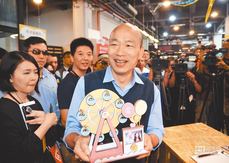 高雄市長韓國瑜捧著手作的愛情摩天輪,手作上有他與女兒韓冰的照片,他笑得開心。(林瑞益攝)