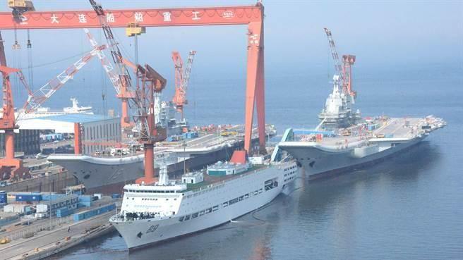 解放軍首艘航母「遼寧」艦和第一艘自製航母2018年7月21日並列,停靠在大連造船廠碼頭,首度呈現上演雙艦合璧的畫面。(中新社)