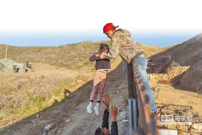 在美墨邊境墨西哥一側的蒂華納,一名來自宏都拉斯的移民在邊界牆上將一名小女孩抱給她在美國一側的爸爸。美國總統川普決定宣布國家進入緊急狀態,以繞過國會取得美墨邊界建牆經費。(美聯社)