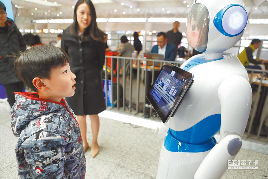 小男孩在虹橋火車站5G體驗區內與智慧機器人互動。(中新社)