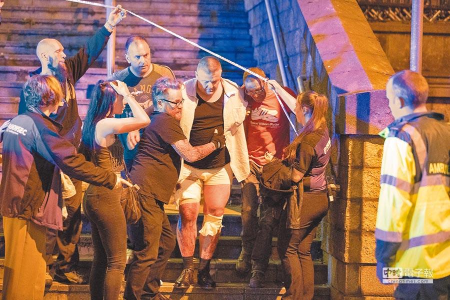 2017年5月22日晚間,英國曼徹斯特競技場一場演唱會近尾聲時,發生自殺炸彈爆炸攻擊。圖為一名傷者正被救護人員送醫治療。英國籍IS新娘貝根認為,這是IS合理的報復舉措。(美聯社)