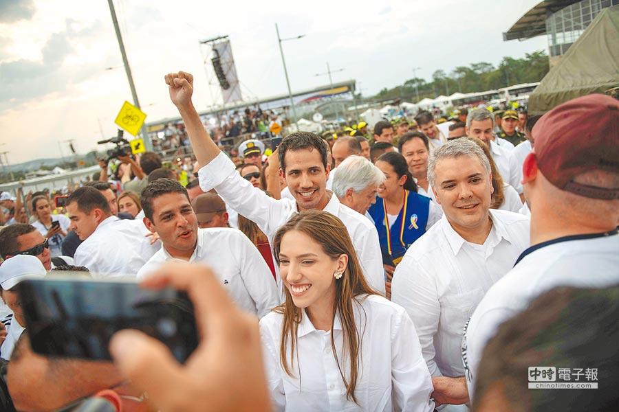 委內瑞拉反對派領袖瓜伊多(舉手者)與哥倫比亞總統杜克(右),22日在哥倫比亞邊境城市庫庫塔舉辦的慈善演唱會上現身。(路透)