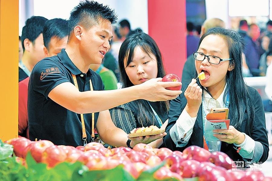 2018年11月7日,上海舉辦首屆進博會,工作人員(左)為參觀者介紹從美國進口的蘋果。(新華社)