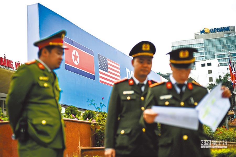 川金二會即將登場,越南警方24日已加強戒備,警察背後為繪有美國與北韓國旗的看板,歡迎兩位元首蒞臨。(法新社)