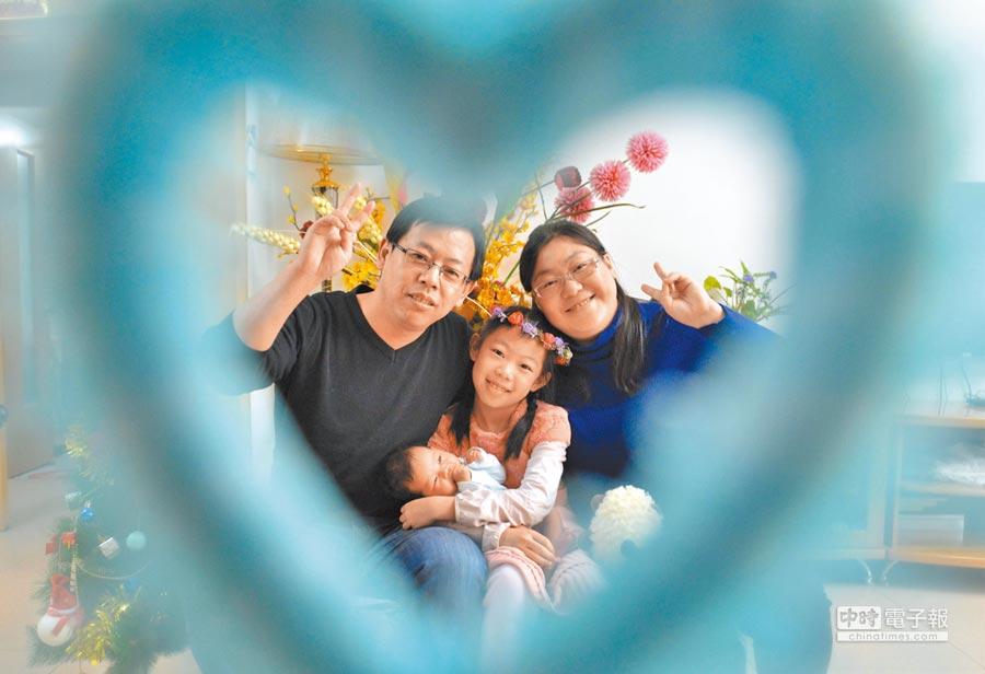 大陸二孩經濟火了!圖為2015年12月14日,內蒙古呼和浩特市一對夫婦帶著9歲的大女兒與剛滿月的小女兒拍全家福。(新華社)