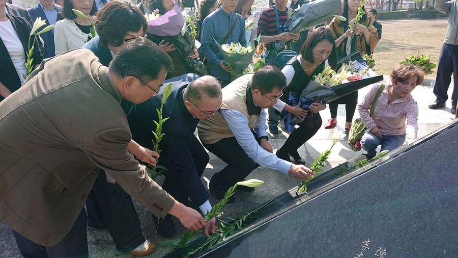 台南市長黃偉哲(米白色背心者)帶著家屬向紀念碑遞上百合花。(程炳璋攝)