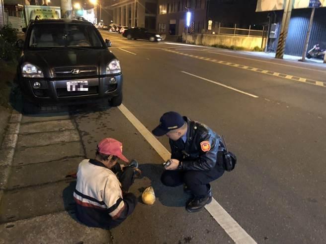 老翁寒夜路蹲坐路旁,暖警細心照料助返家。(警方提供)