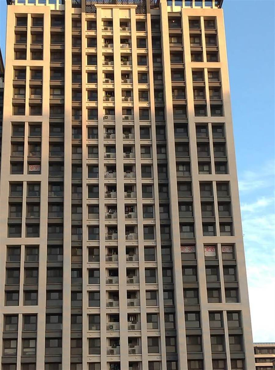 桃園市高鐵青埔站旁的豪宅建案「寶徠花園」,被網友拍下有住戶在窗戶外貼上8個紅色「冤」字,引發熱烈討論。(圖/翻攝自臉書)