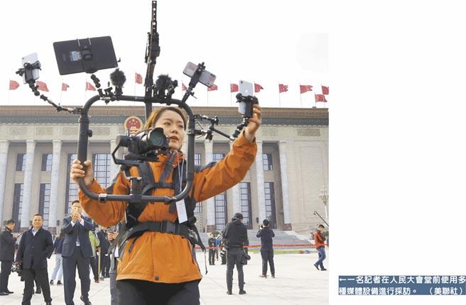 一名記者在人民大會堂前使用多種媒體設備進行採訪。(美聯社)