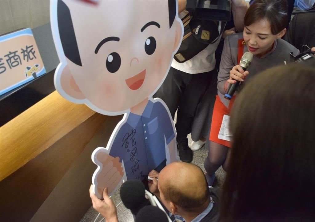 韓國瑜在高雄樺舍商旅的Q版韓國瑜立像上簽名。圖:遠航提供