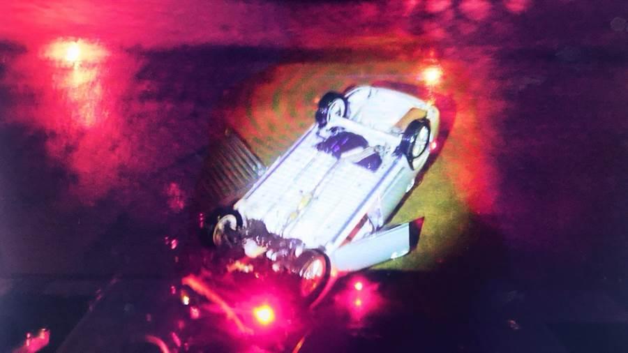 台中市凌晨發生一起自小客車撞毀護欄直衝麻園溪底意外,車輛倒栽翻覆,摔得四輪朝天。(陳淑芬翻攝)