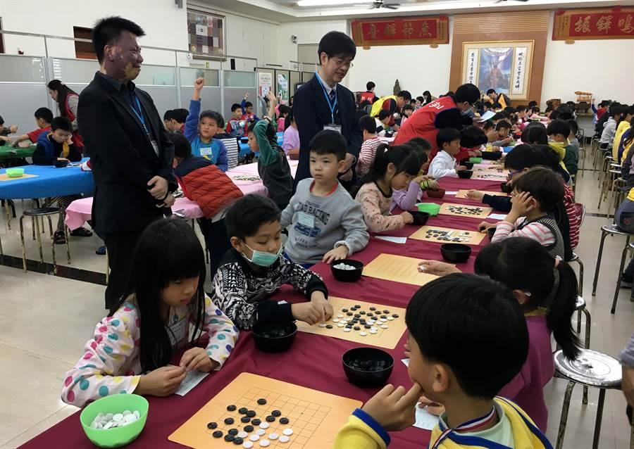 小朋友參加九華山地藏王盃圍棋賽,旅日「棋聖」王立誠(左後)、「紅面棋王」周俊勳(左前)觀賽。(廖素慧攝)