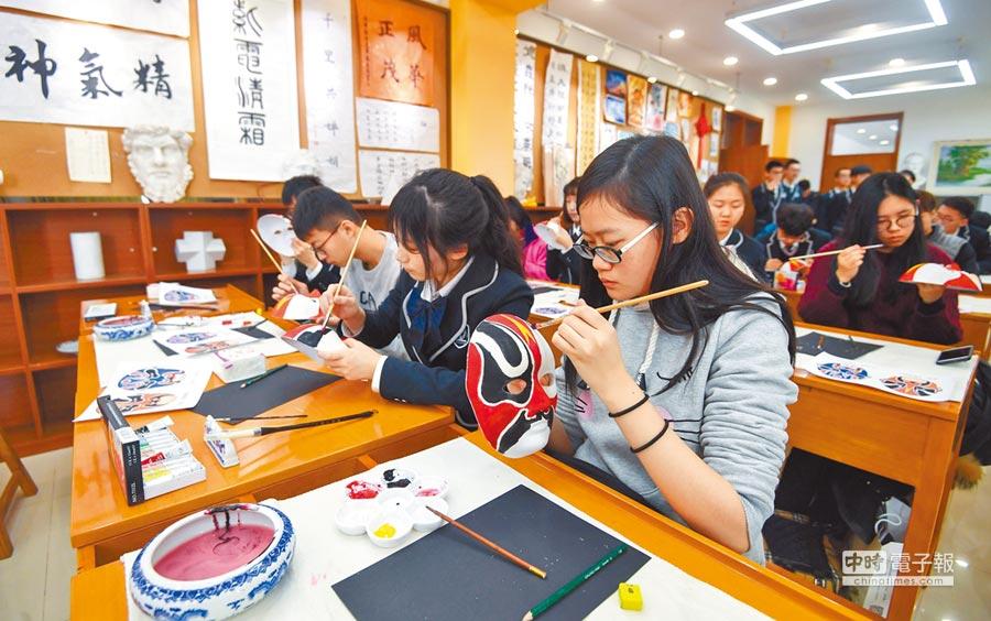 1月22日,來自台灣的中學生到北京市海淀實驗中學與大陸同學交流,一起畫京劇臉譜。(新華社)