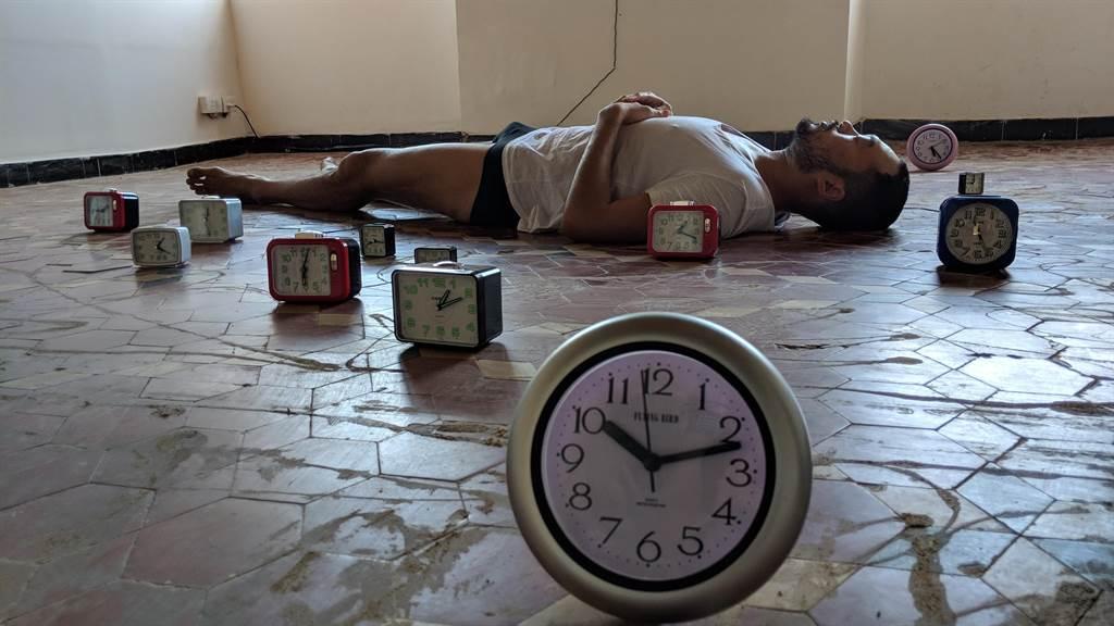 台灣藝術家林人中近年在歐陸闖出一片天,將在布魯塞爾表演雙年展演出作品《時間是圓的》,從鬧鐘叫人起床、入睡的行動中,表現時間的面貌。圖為日前在印度演出的版本《在謝德慶與河原溫之間睡去》。(林人中提供)