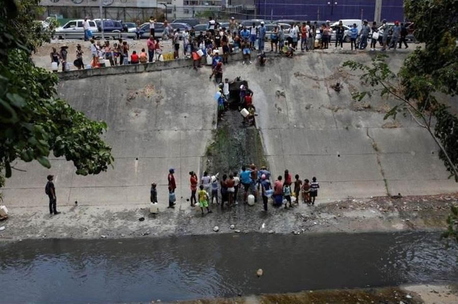 卡拉卡斯市民在一個大排水管外取水,那是少數水質透明的水源。(圖/路透社)