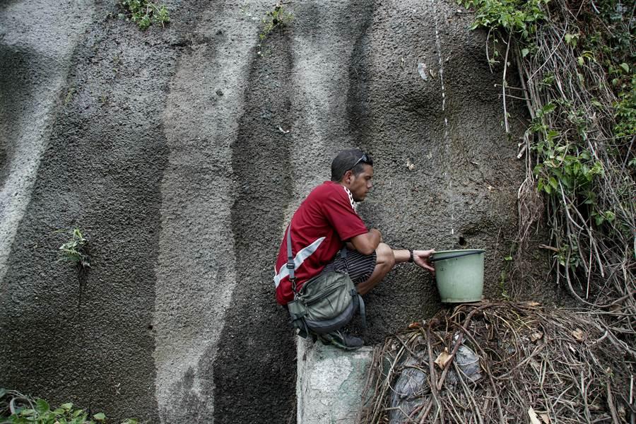 沒有自來水,委內瑞拉人民只能各自想辦法,山壁的涓滴細流也很珍貴。(圖/美聯社)