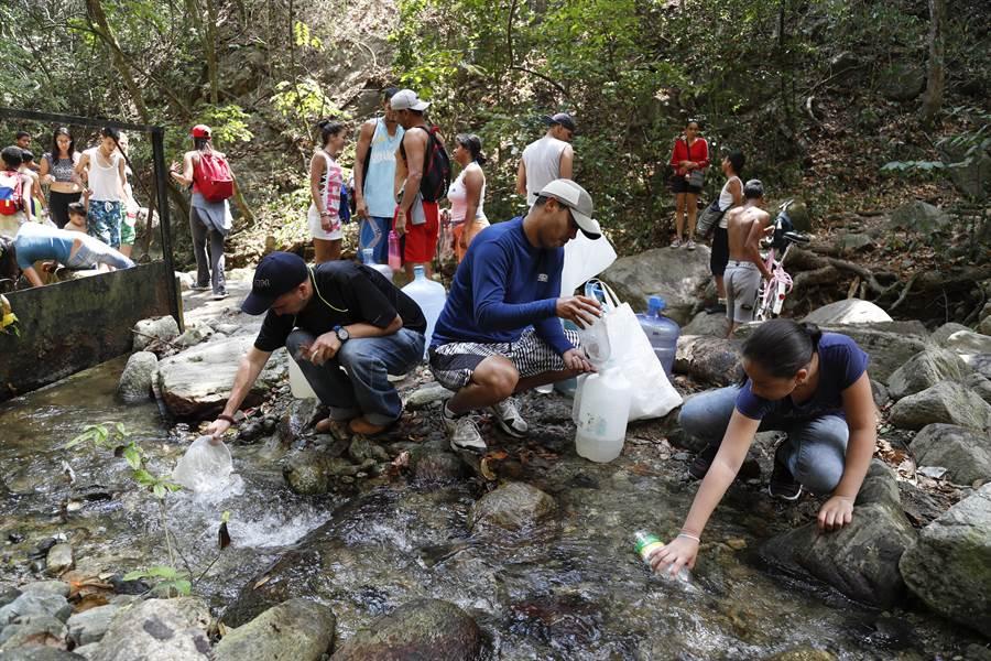 山裡的小溪流成了比較可靠的水源,委內瑞拉人到山區取水。(圖/美聯社)