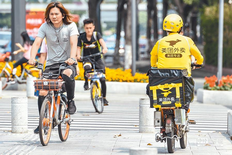 美團外賣員與騎行摩拜單車的民眾。(中新社資料照片)