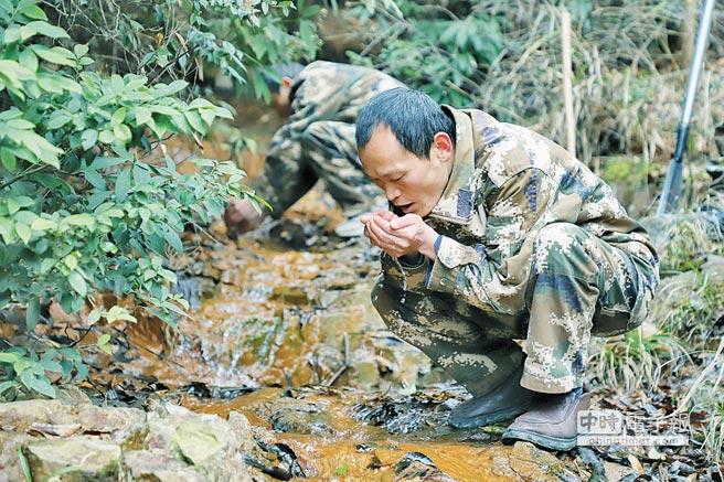 3月10日,張忠(前)和張華在林間喝山泉水止渴。(中新社)