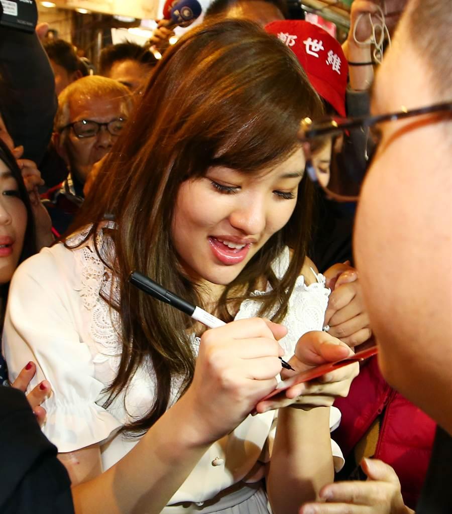 韓國瑜的女兒韓冰(見圖)至三和夜市掃街拜票,受到支持者熱情歡迎,過程中雖然群被民眾包圍、寸步難行,韓冰還是開心的為民眾簽名。(資料照 陳信翰攝)