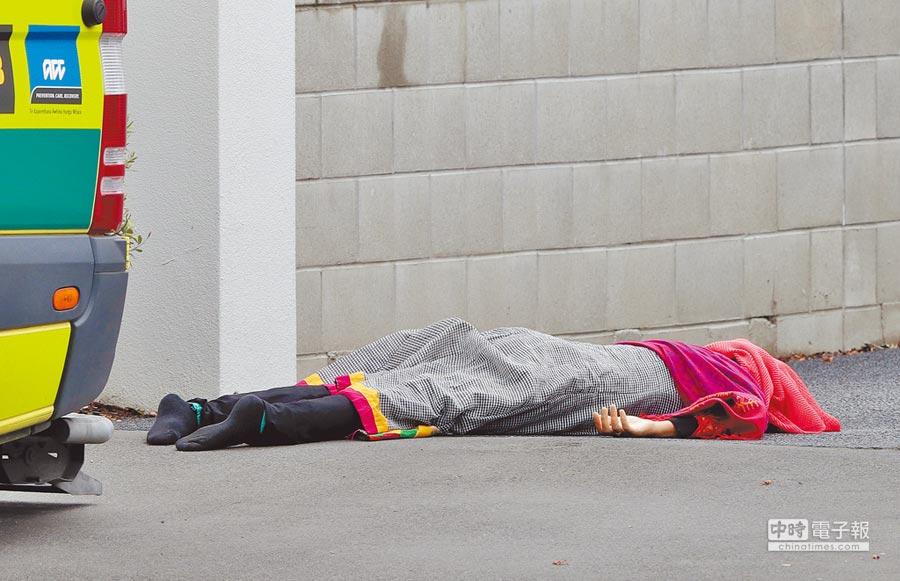 在基督城市中心一座清真寺外的人行道上,躺著一具罹難者遺體。(美聯社)