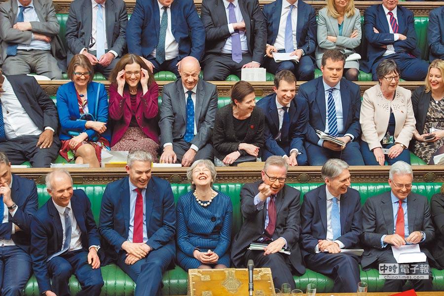 英國首相梅伊(下排左三)出席國會下議院就其所提,將脫歐日期從3月29日至少延後3個月至6月底的議案進行辯論。(路透)