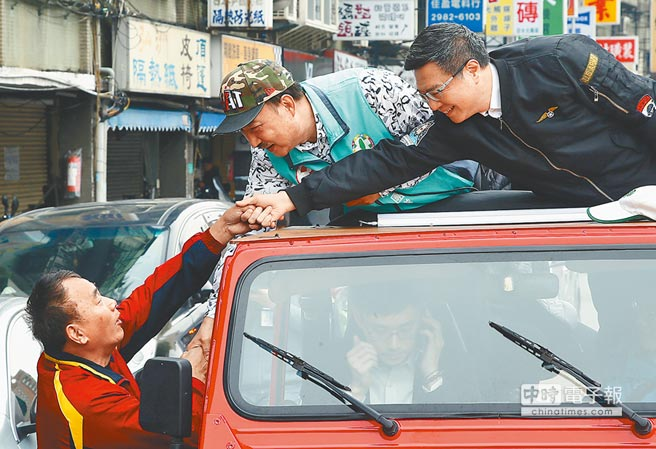 民進黨主席卓榮泰(右)陪同新北市三重區立委當選人余天(右二)以車隊掃街謝票,兩人彎腰向選民握手致謝。(劉宗龍攝)