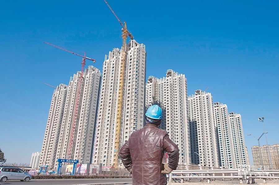 建築工人經過山西太原一處正在建設中的大樓。(中新社資料照片)