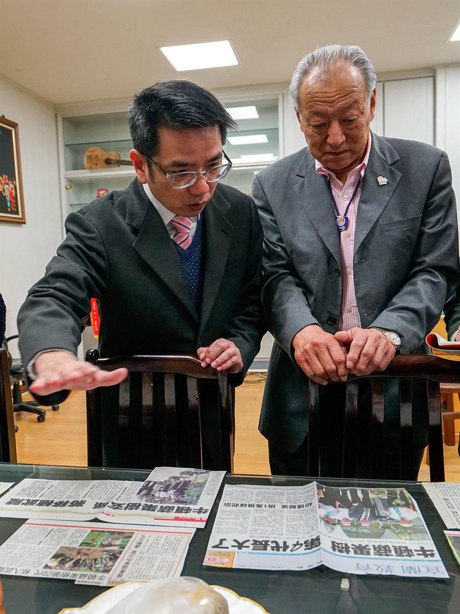 宜蘭市長江聰淵(左)向木內義範出示分株第4代蘋果樹的剪報,盼能再分株第5代蘋果樹。(李忠一攝)