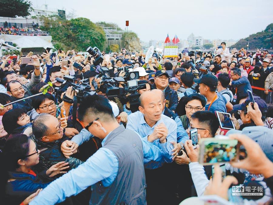 高雄市長韓國瑜去年跨年時到西子灣送夕陽,受到媒體與熱情民眾包圍。(本報資料照片)