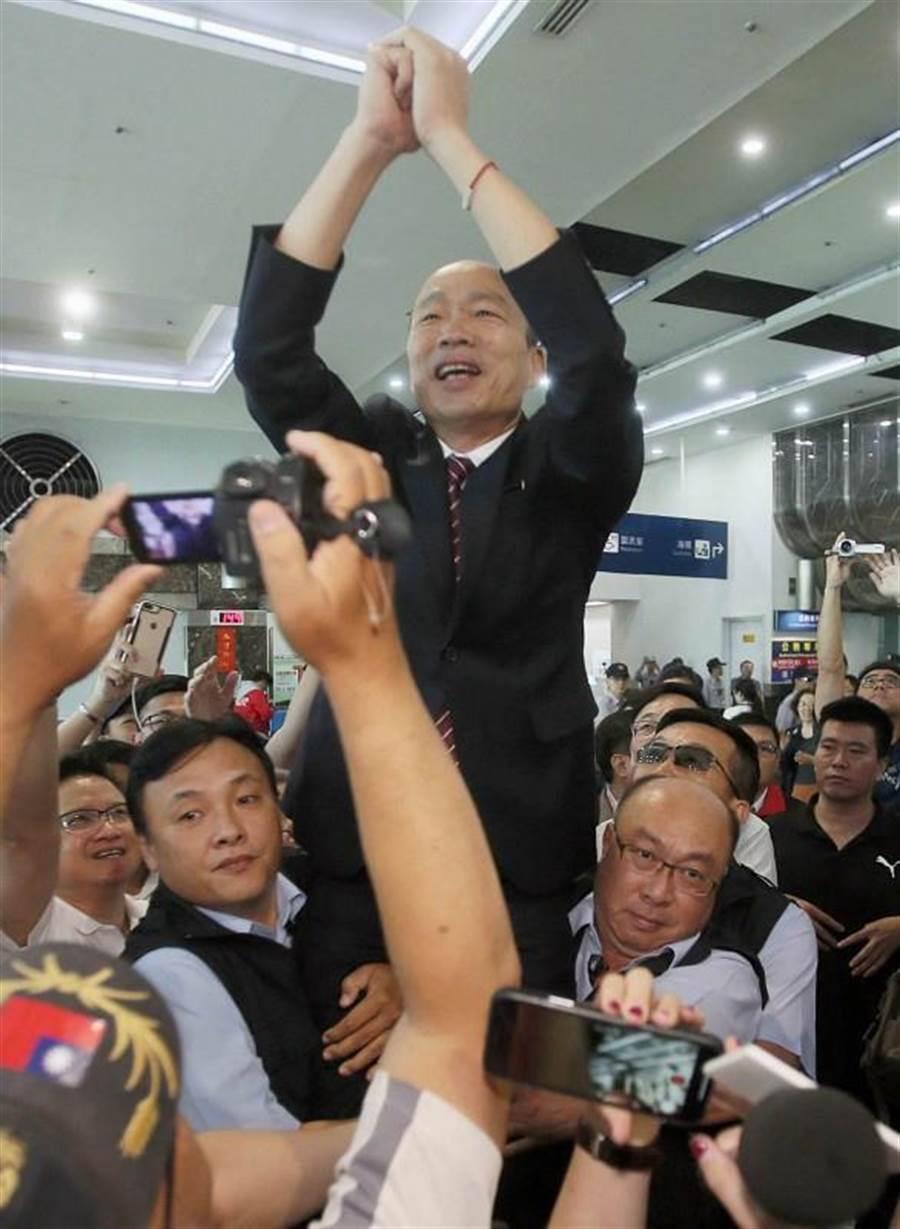 高雄市長韓國瑜28日結束出訪港澳大陸行,抵達高雄小港機場時受到萬名韓粉、民眾熱情接機,韓國瑜為向在場所有人揮手致意,身旁2名男子以抱大腿方式將韓市長高高舉起。(高市府提供)