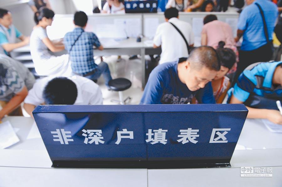 深圳市公安局出入境管理處梅林辦證大廳,前來辦證的非深戶籍人員在填寫申請表。(新華社資料照片)