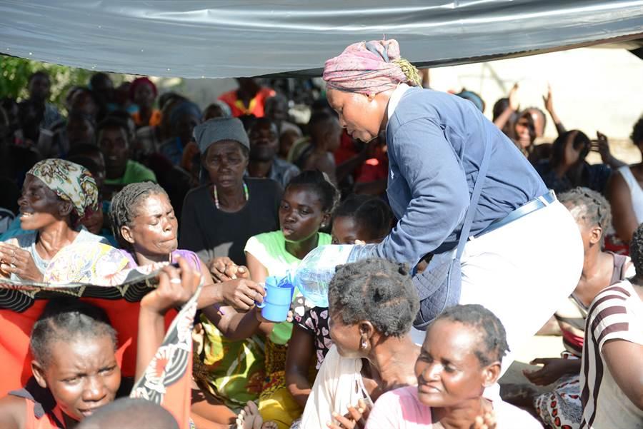 災後缺乏乾淨的飲用水,慈濟志工一一為鄉親倒上淨水,解災民的渴。(圖/慈濟基金會提供)