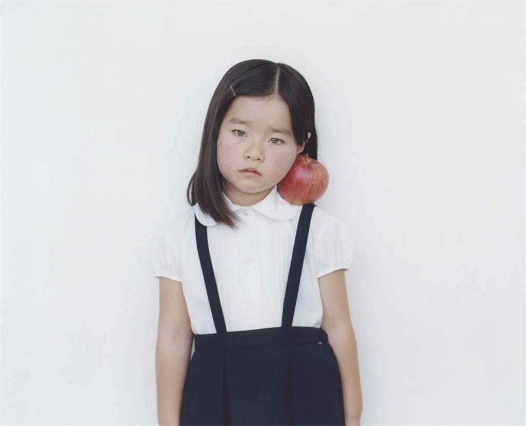 日本影像大師橫浪修代表作品「1000 Children」系列,以穿著校服的小女孩肩膊夾著水果為創作素材。(新光三越提供)