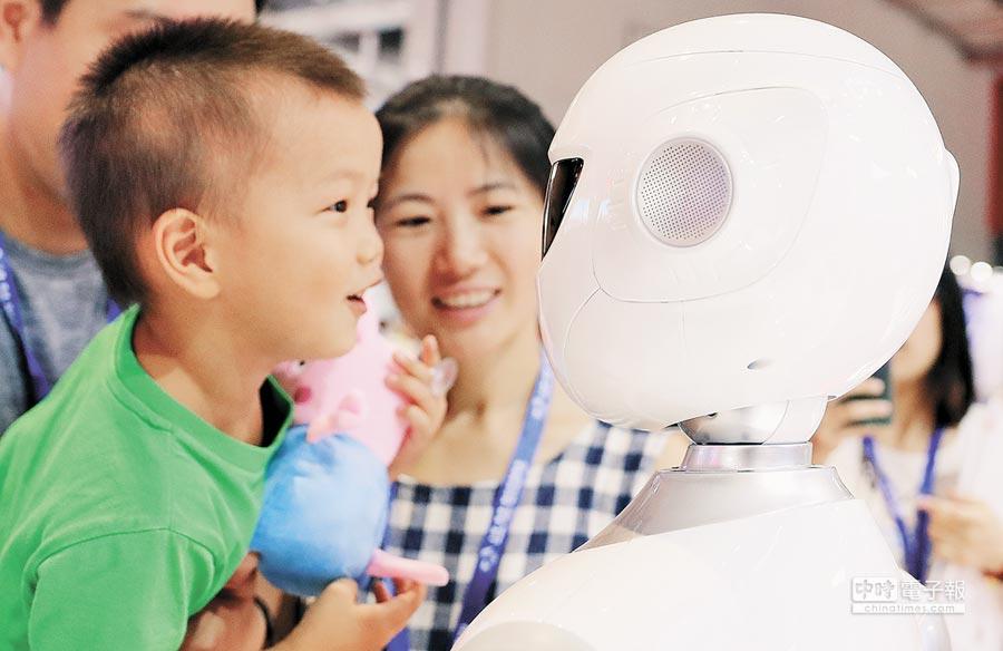 一名小朋友在上海國際工業博覽會上,與機器人互動。(新華社資料照片)
