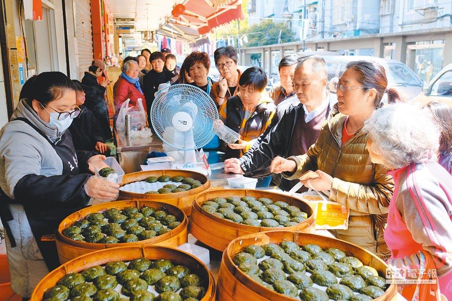 4月1日,清明將至,杭州一家老字號小吃店裡純手工製作的青團大受歡迎,引市民排隊搶購。(中新社)
