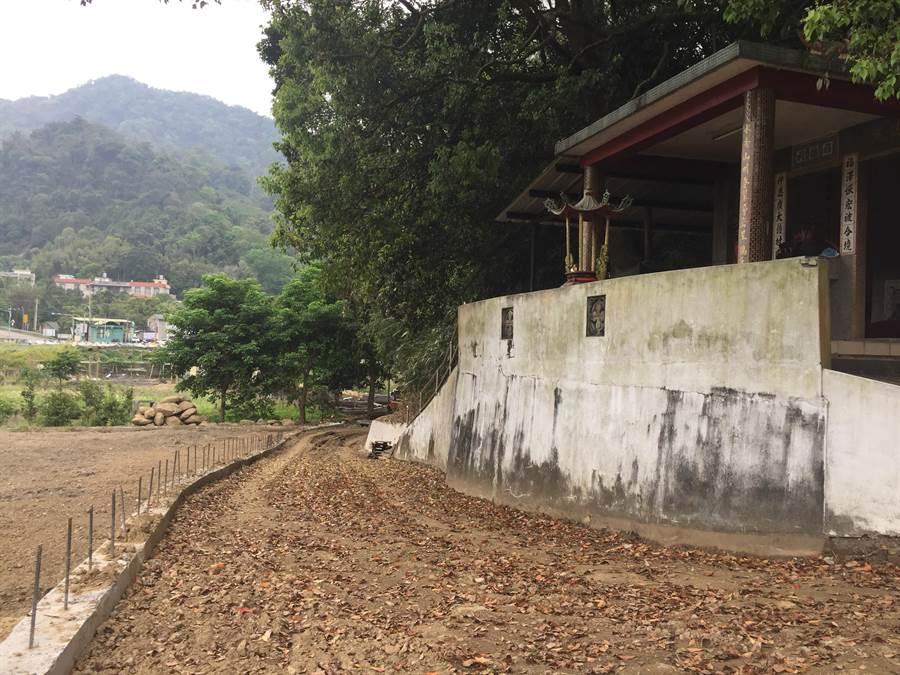 施工路段旁有土地公廟,民眾若要參拜得先走過充滿泥濘的道路,還要擔心失足會遭鋼筋刺傷。(巫靜婷攝)